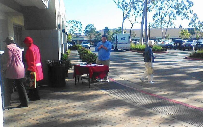 A man saying he was collecting signatures on a petition opposing the planned Museum House development stands outside Ralphs in the Westcliff shopping center in Newport Beach on Friday.