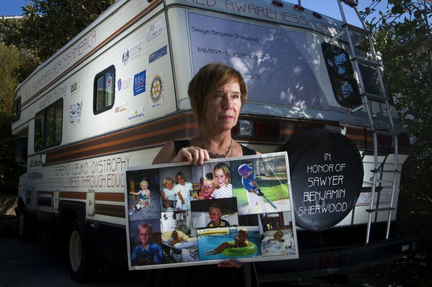 Janis Sherwood of Vista stands in front of the RV she drove more than 44,000 miles to promote awareness of adrenoleukodystrophy, the rare genetic disorder that killed her son, Sawyer, in 2003.