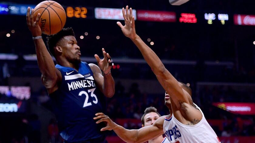 Minnesota Timberwolves' Jimmy Butler (23) passes around Clippers' Wesley Johnson (33) and Danilo Gallinari (8) during the first half at Staples Center on Wednesday.