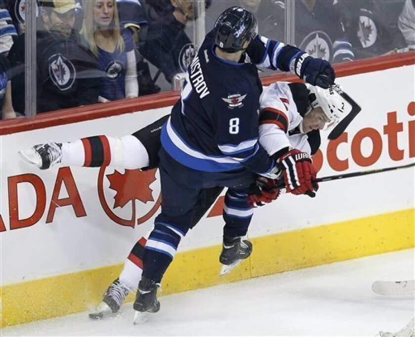 Winnipeg Jets' Alexander Burmistrov (8) takes out New Jersey Devils' Marek Zidlicky (2) during the first period of an NHL hockey game in Winnipeg, Manitoba, on Thursday, Feb. 28, 2013. (AP Photo/The Canadian Press, John Woods)