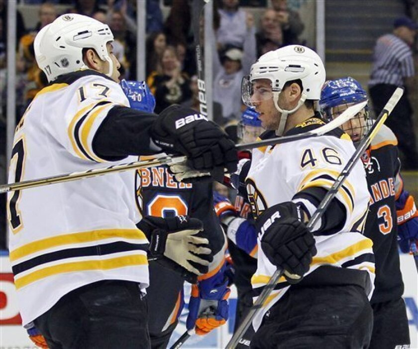 Boston Bruins' Milan Lucic (17) congratulates teammate David Krecji (46) after Krecji scored a goal against the New York Islanders during the first period of an NHL hockey game at the Nassau Coliseum in Uniondale, N.Y., Saturday, March 31, 2012. (AP Photo/Paul J. Bereswill)