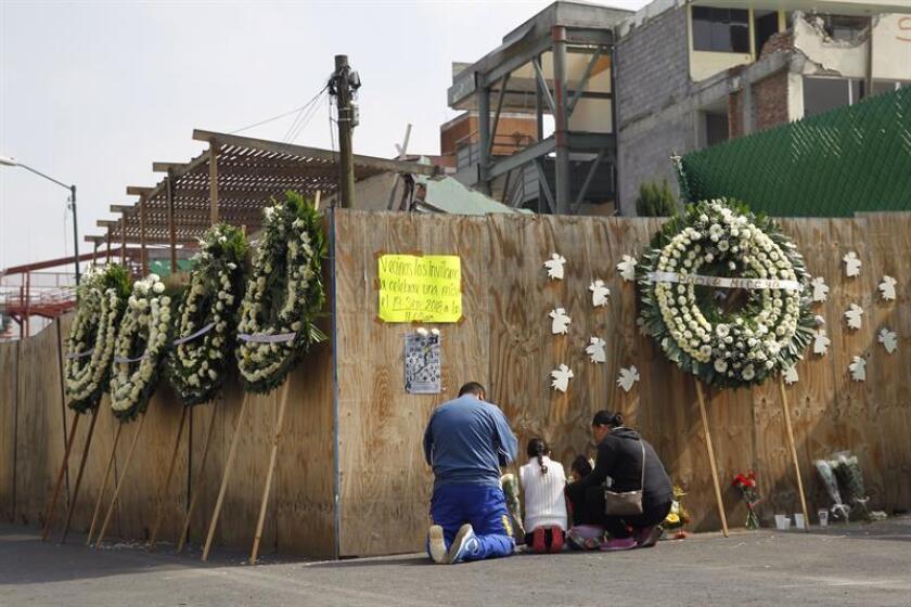 Familiares de algunos de los niños que perdieron la vida en el Colegio Rebsamen durante el terremoto de 2017 en Ciudad de México (México), oran junto un muro que resguarda las ruinas de esta escuela hoy, miércoles 19 de septiembre de 2018. EFE