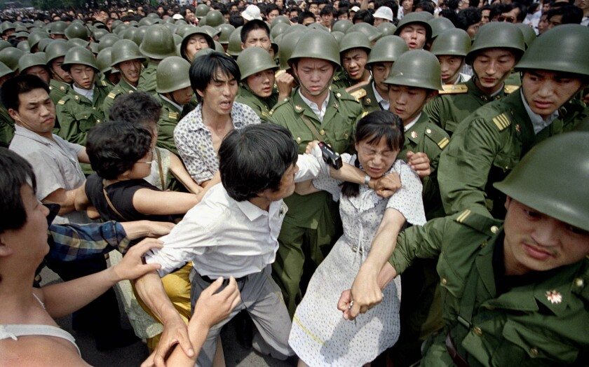 A young woman is caught between civilians and Chinese soldiers, who were trying to remove her from a