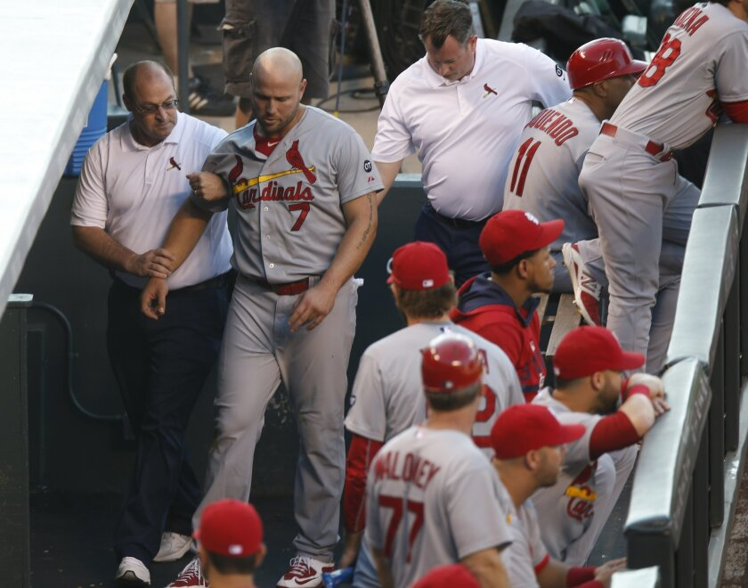 St. Louis Cardinals left fielder Matt Holliday, center, is led through the dugout by head trainer Greg Hauck, left, and assistant trainer Chris Conroy after Holliday hurt his leg while pursuing a fly ball against the Colorado Rockies in the second inning of a baseball game Monday, June 8, 2015, in Denver. (AP Photo/David Zalubowski)