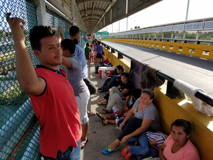 Central American families are camped out on a border bridge between Ciudad Miguel Aleman, Mexico, and Roma, Texas. The man in red in the foreground is Marco Estrada from Honduras.