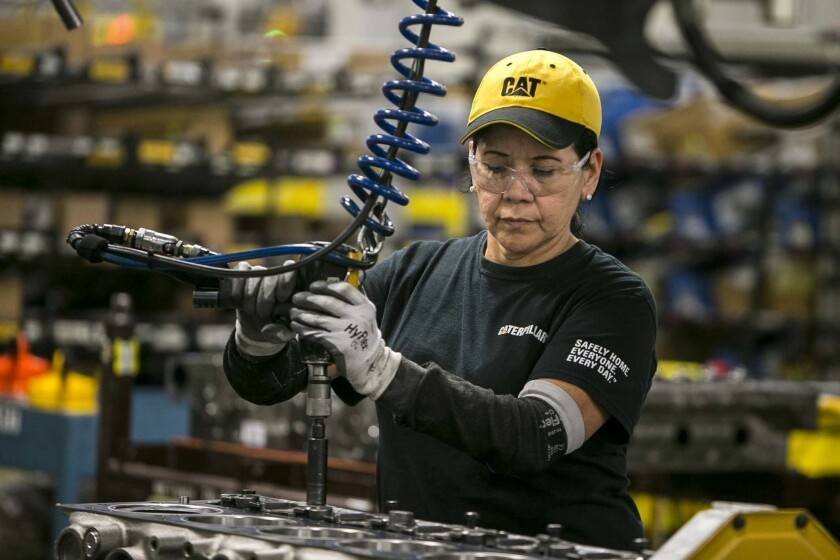 In this June 13, 2018, photo, Margarita Cardenas attaches an engine head at Caterpillar's engine manufacturing plant in Seguin, Texas.