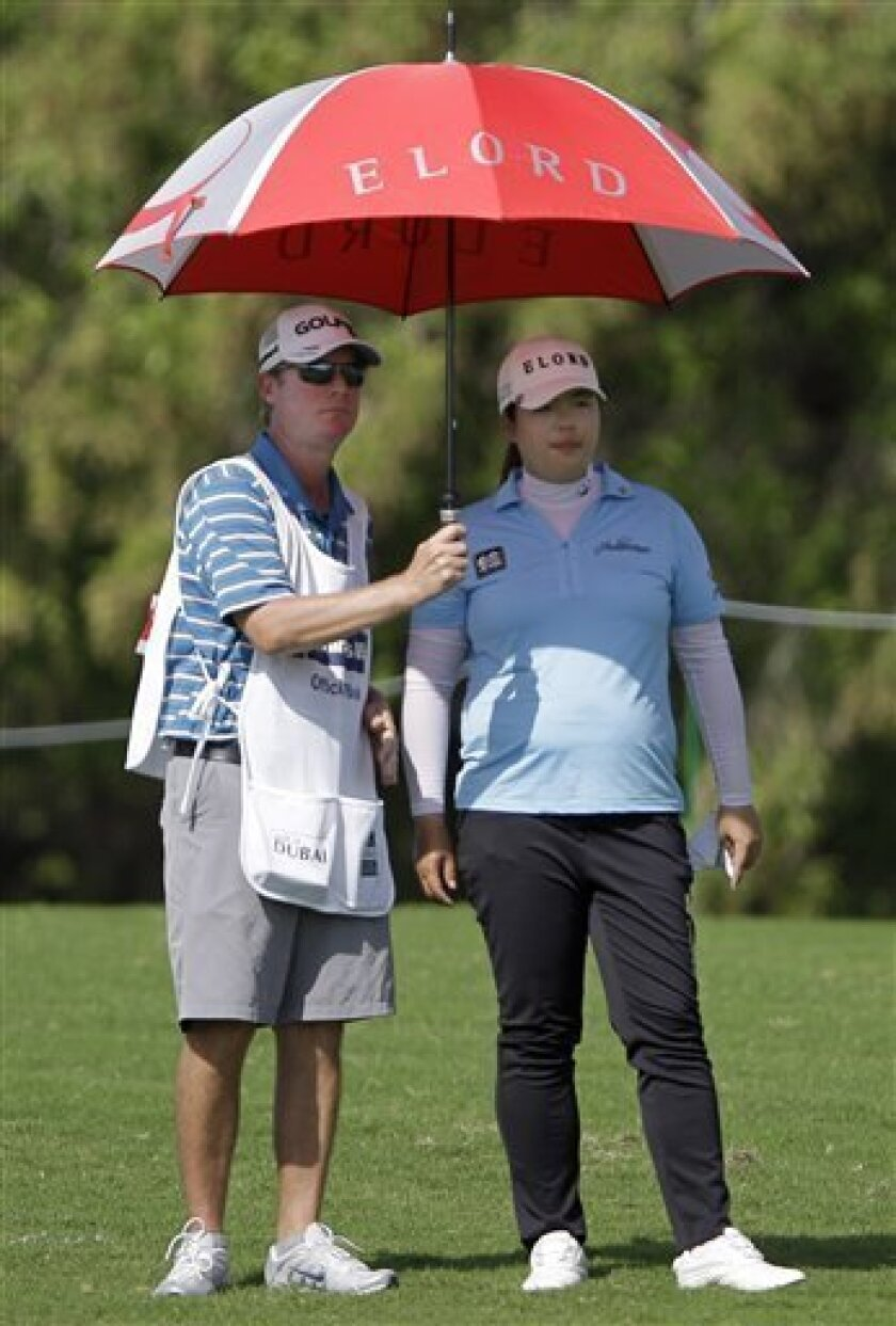 Feng Shanshan from China, right, talks with her caddie before she plays a ball on the 3rd hole during the round one of Dubai Ladies Masters golf tournament in Dubai, United Arab Emirates, Wednesday Dec. 5, 2012. (AP Photo/Kamran Jebreili)