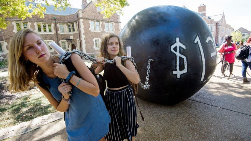 Students pull a ball-and-chain prop, representing student debt, at Washington University in St. Louis in 2016.
