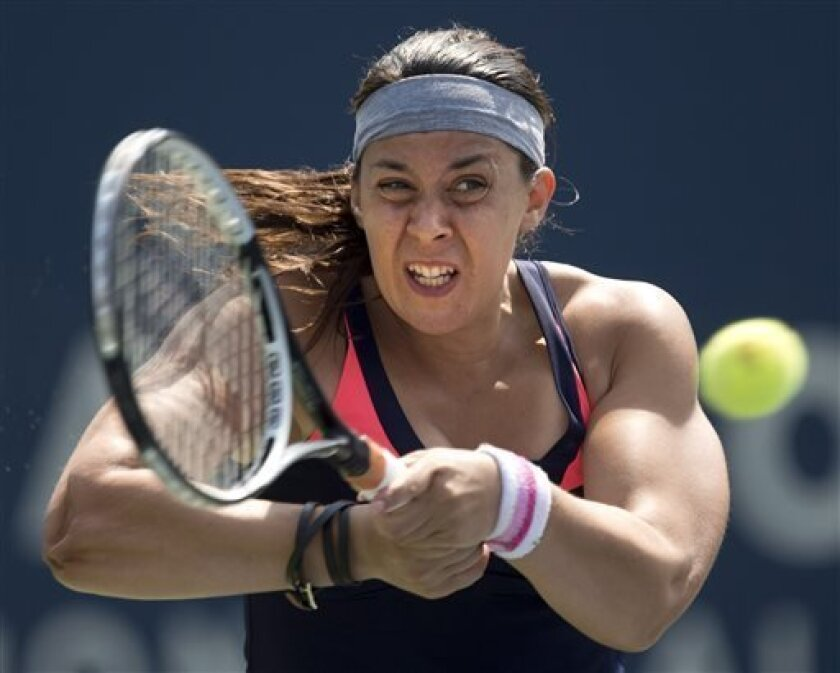 Marion Bartoli, of France, returns a shot to Lauren Davis, of the United States, at the Rogers Cup women's tennis tournament in Toronto on Wednesday, Aug. 7, 2013. (AP Photo/The Canadian Press, Frank Gunn)