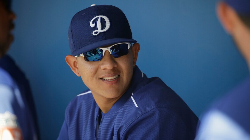 Pitcher Julio Urias talks to teammates in the Dodgers dugout during spring training.