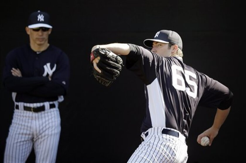 FILE - In this Feb. 16, 2013 file photo,New York Yankees' Phil Hughes, right, pitches as manager Joe Girardi looks on during a workout at baseball spring training in Tampa, Fla. Hughes could be sidelined for two weeks because of a bulging disk that will be treated with anti-inflammatory medication