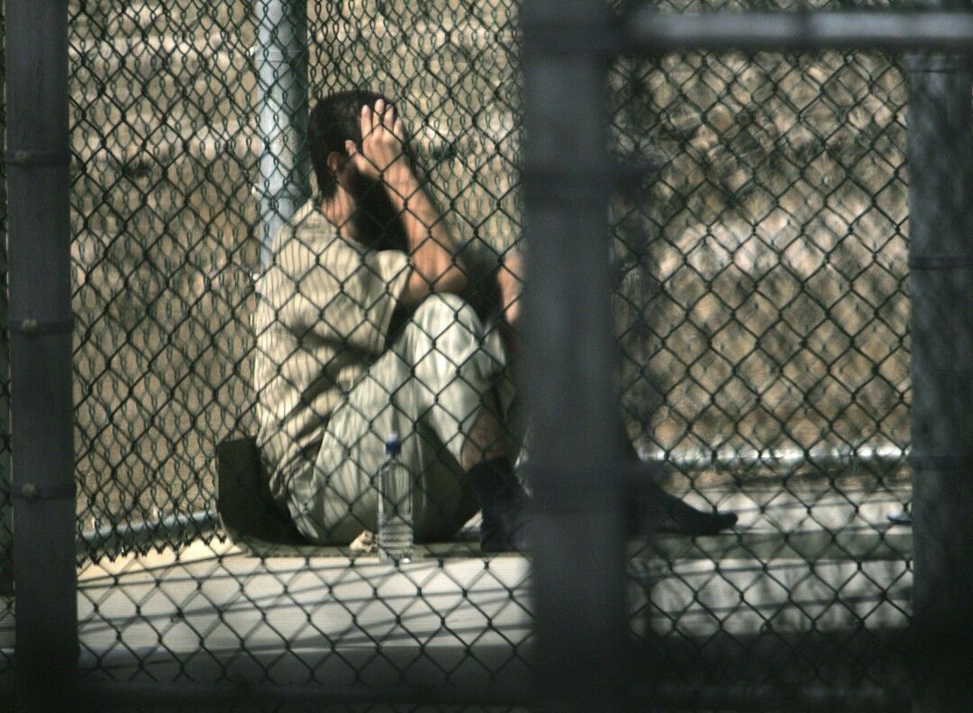 A man with dark hair and beard holds a hand to his face as he sits behind a wire fence