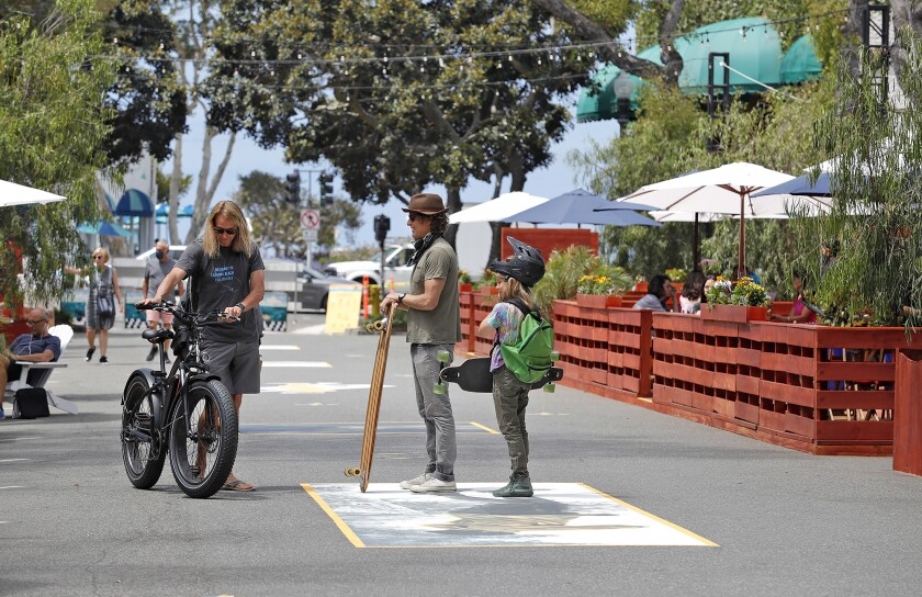 A few locals gather on the Promenade on Forest in downtown Laguna Beach, which opened to the public in June 2020.