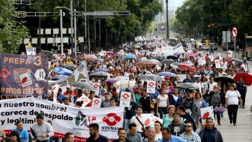 Union workers march in Mexico City on Wednesday to demand that Mexico drop out of the NAFTA renegoti