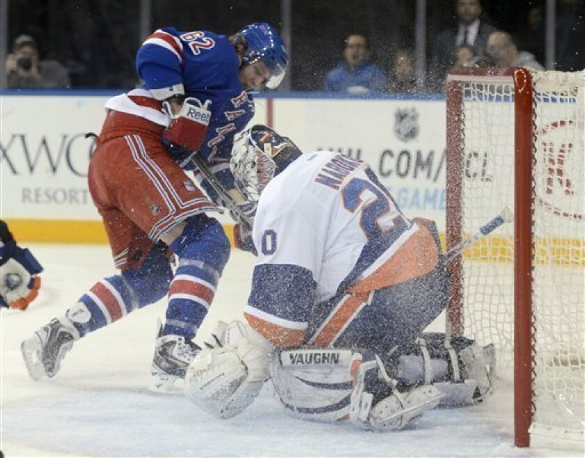 New York Rangers' Carl Hagelin, left, forces the puck past New York Islanders goalie Evgeni Nabokov for a power-play goal during the second period of an NHL hockey game at Madison Square Garden in New York, Thursday, Feb. 14, 2013. (AP Photo/Henny Ray Abrams)