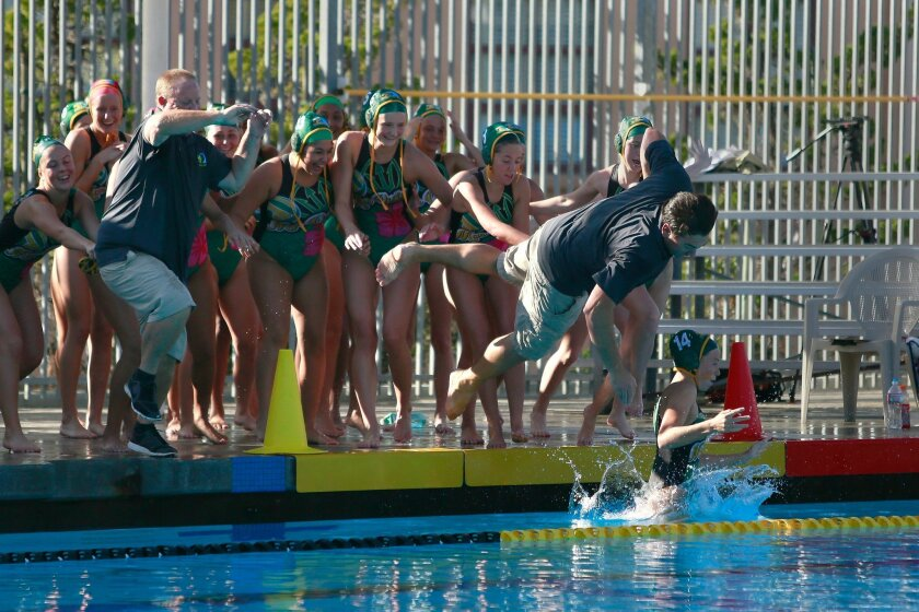 Mar Vista head coach Chad Kavanagh is thrown in to the pool celebrating a  win against Scripps Ranch