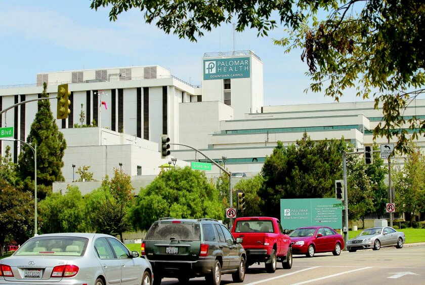 A new temporary sign is posted on the highest tower of the Palomar Health Downtown Campus. The place will be getting an extensive renovation. In the foreground is traffic on Grand Avenue in this view looking east.