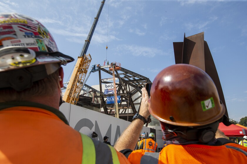 Soren Stufkosky, left, and Brad McGlothlin watch at the site of the new Orange County Museum of Art on Tuesday.