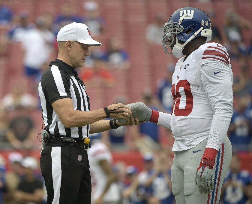 NFL referee Clete Blakeman, check's the bandage on New York Giants defensive end Jason Pierre-Paul's hand before an NFL football game against the Tampa Bay Buccaneers Sunday, Nov. 8, 2015, in Tampa, Fla. Pierre-Paul is playing in his first game since injuring his hand with fireworks during the off-