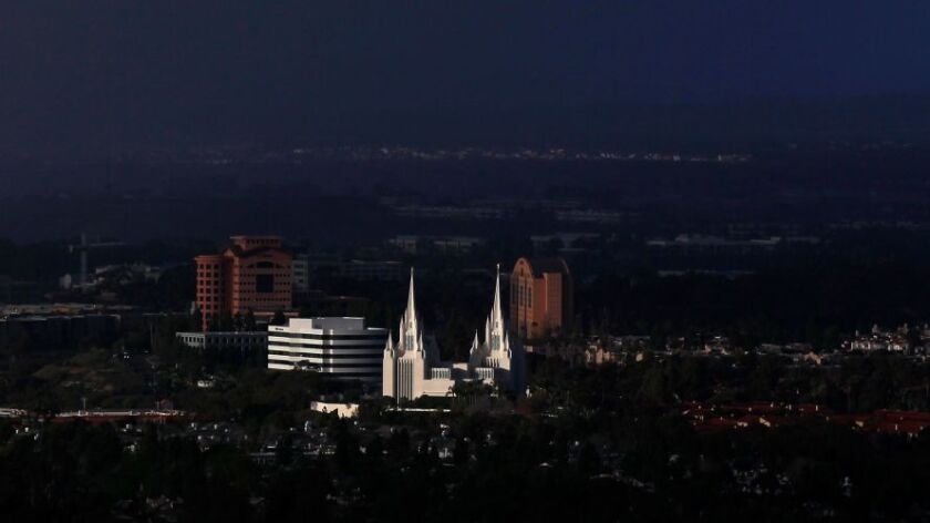 Late afternoon light shines on the San Diego California Temple in La Jolla as rain falls behind it.