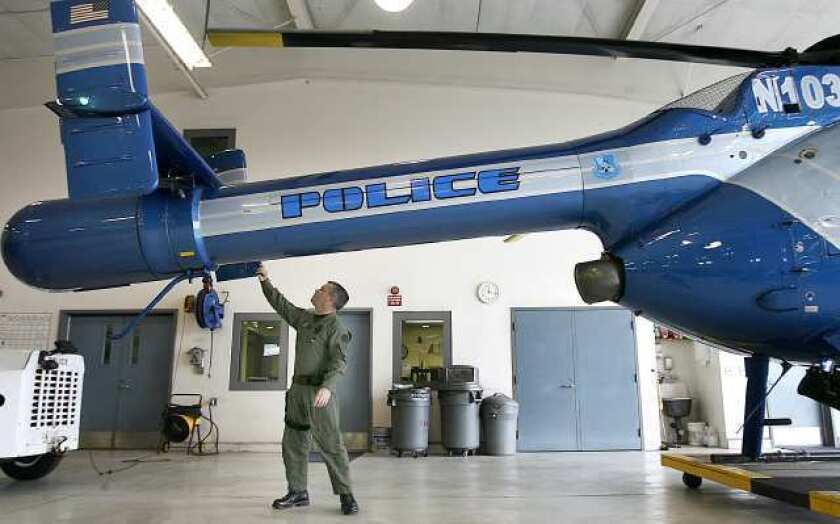 An officer inspects a police helicopter at Bob Hope Airport.