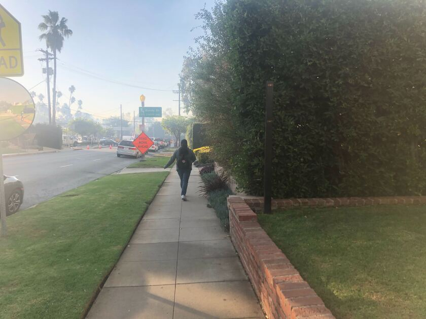 Ana Martinez walks through a neighborhood evacuated in the Getty fire on Monday.