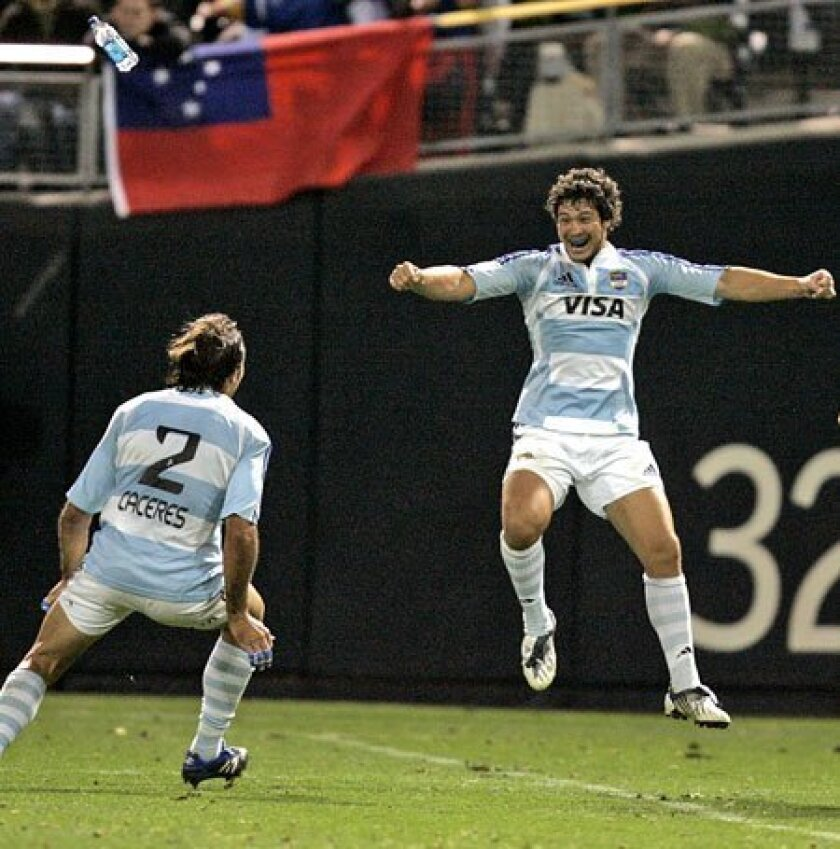 Argentina players celebrate their 19-14 upset victory over England in the USA Sevens championship match last night at Petco Park. (Crissy Pascual / Union-Tribune)