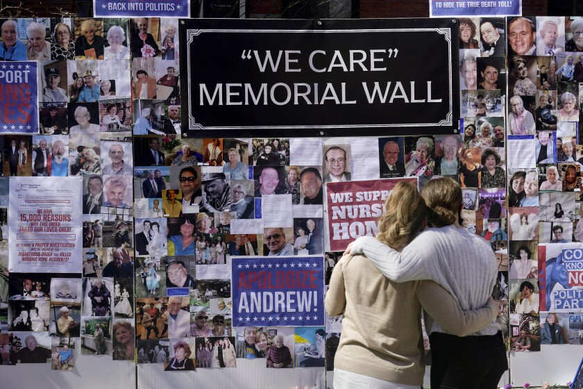 Two women look at a  memorial wall