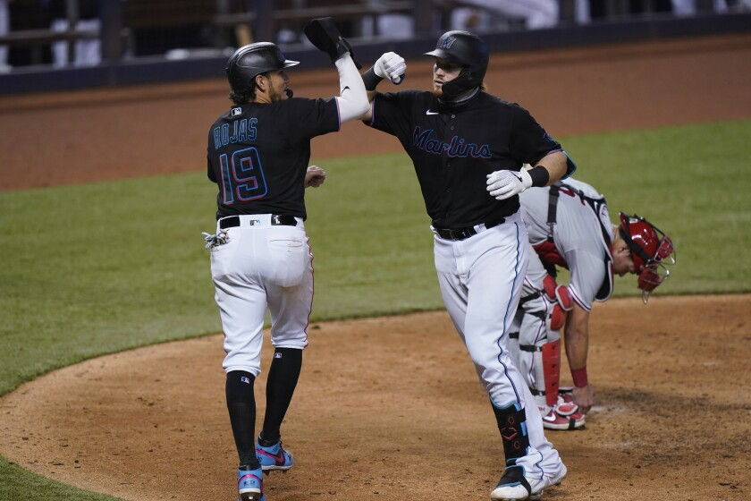 Miami Marlins' Miguel Rojas (19) congratulates Chad Wallach after Wallach hit a home run that also scored him during the sixth inning of the second game of a baseball doubleheader against the Philadelphia Phillies, Sunday, Sept. 13, 2020, in Miami. (AP Photo/Wilfredo Lee)