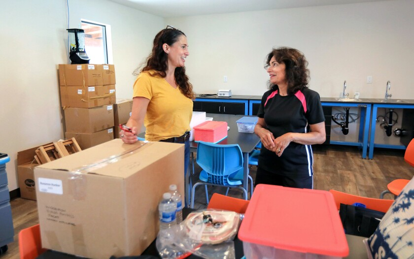 In a science classroom at the new Middle School Campus of The Rhoades School engineering teacher Alicia Trout, at left, and science teacher Roxanne Hunker, at right, catch up on how they spend their summer vacations. They are getting their classrooms read