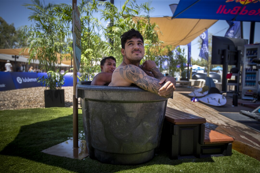 Gabriel Medina, front, two-time WSL world champion from Brazil, and Seth Muniz, of Hawaii, sit in the ice tub.