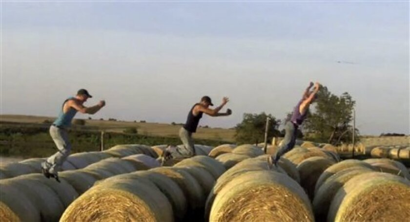 """This frame grab from video shows Assaria, Kan., brothers, from left: Nathan; Kendal and Greg Peterson in their video parody on LMAFO's """"Sexy and I Know It.""""  The parody, that has gone viral on YouTube and Facebook, shows the three brothers rapping their farming mission on the family's Saline County"""