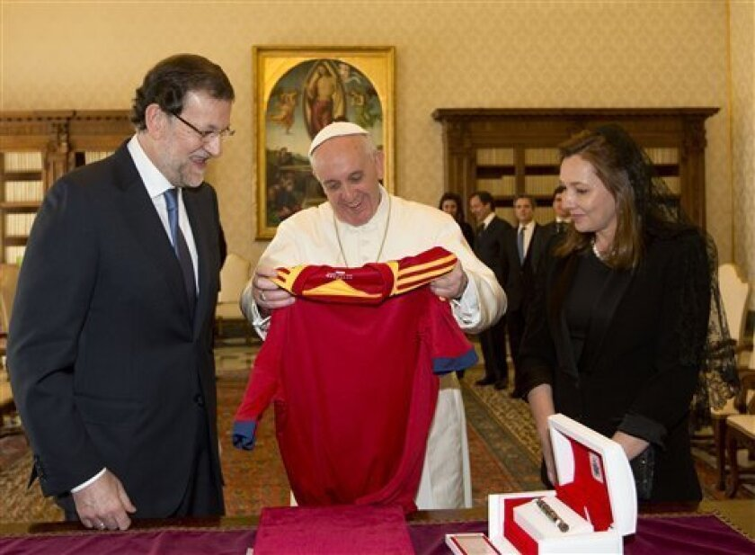 Pope Francis, center, is presented with a jersey of the Spanish national soccer team during his private audience with Spain's Prime Minister Mariano Rajoy and his wife Elvira Fernandez Balboa, right, at the Vatican, Monday, April 15, 2013. (AP Photo/Alessandra Tarantino, Pool)