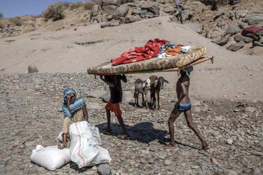 Refugees carry their belongings in eastern Sudan including a mattress and blankets.
