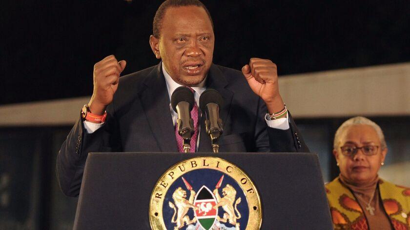 Kenya's President Uhuru Kenyatta, flanked by his wife, Margaret, addresses supporters after winning