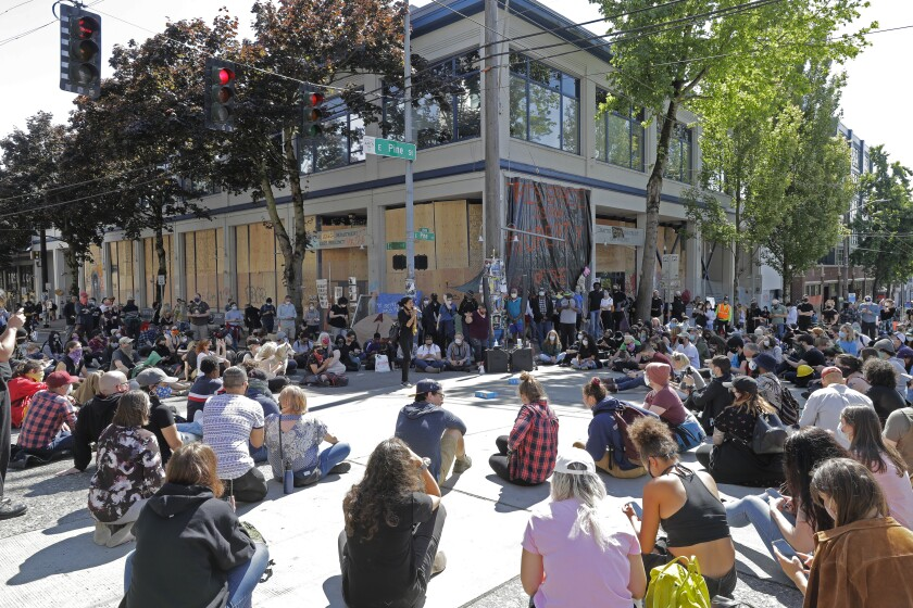 """Protesters listen to a speaker as they sit in front of the Seattle Police Department East Precinct building, which has been boarded up and abandoned except for a few officers inside, Thursday, June 11, 2020, inside what is being called the """"Capitol Hill Autonomous Zone"""" in Seattle. Following days of violent confrontations with protesters, police in Seattle have largely withdrawn from the neighborhood. (AP Photo/Ted S. Warren)"""