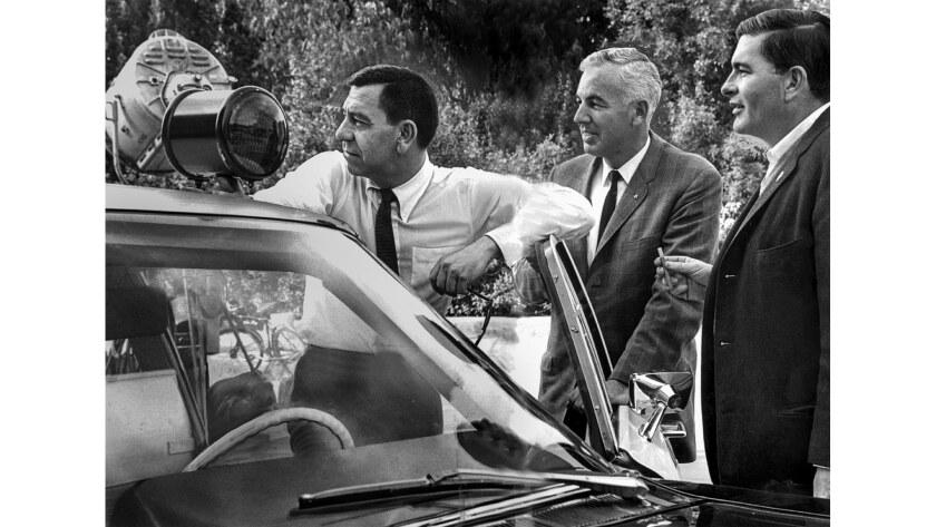 "Feb. 24, 1967: On the set of ""Dragnet,"" actor Jack Webb, left, who plays Sgt. Joe Friday, Los Angeles police Sgt. Dan Cook and associate producer Bob Cinader take a break."