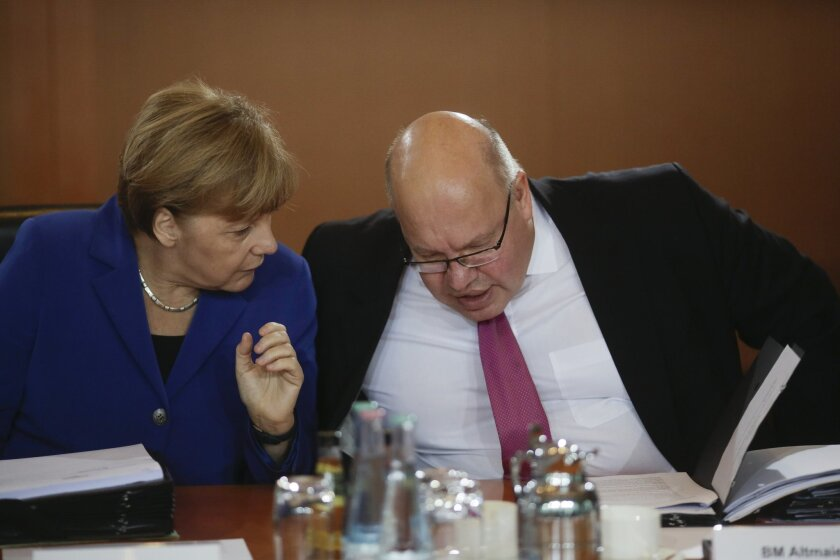FILE - In this Oct. 7, 2015 file picture German Chancellor Angela Merkel, left, talks to the Chief of Staff Peter Altmaier  in Berlin.Peter Altmaier is downplaying a short-lived initiative by the interior minister Thomas de Maiziere to give many Syrians restricted asylum, insisting that the matter
