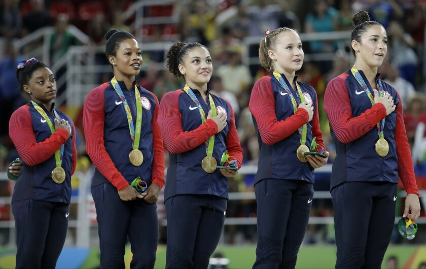 U.S. gymnasts and gold medallists, left to right, Simone Biles, Gabrielle Douglas, Lauren Hernandez, Madison Kocian and Aly Raisman stand for their national anthem during the medal ceremony for the artistic gymnastics women's team at the 2016 Summer Olympics in Rio de Janeiro, Brazil, Tuesday, Aug.