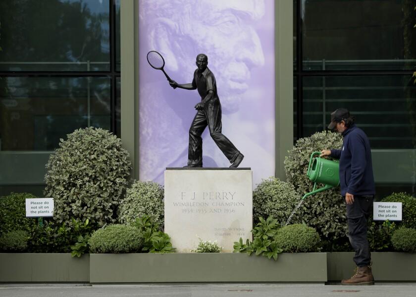 Un jardinero riega las plantas junto a una estatua de Fred Perry, un ex campeón de Wimbledon