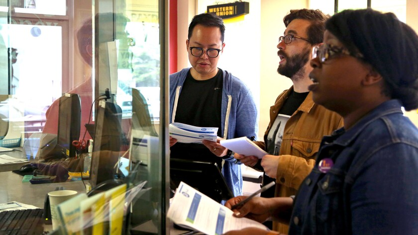 Ray Chay, left, director of operations at a high-interest consumer lending company, L.A. Times staff writer James Rufus Koren and Sybil Mulokwa, a manager at a company that develops software for small banks and credit unions do transactions at a Money Mart in Hollywood.