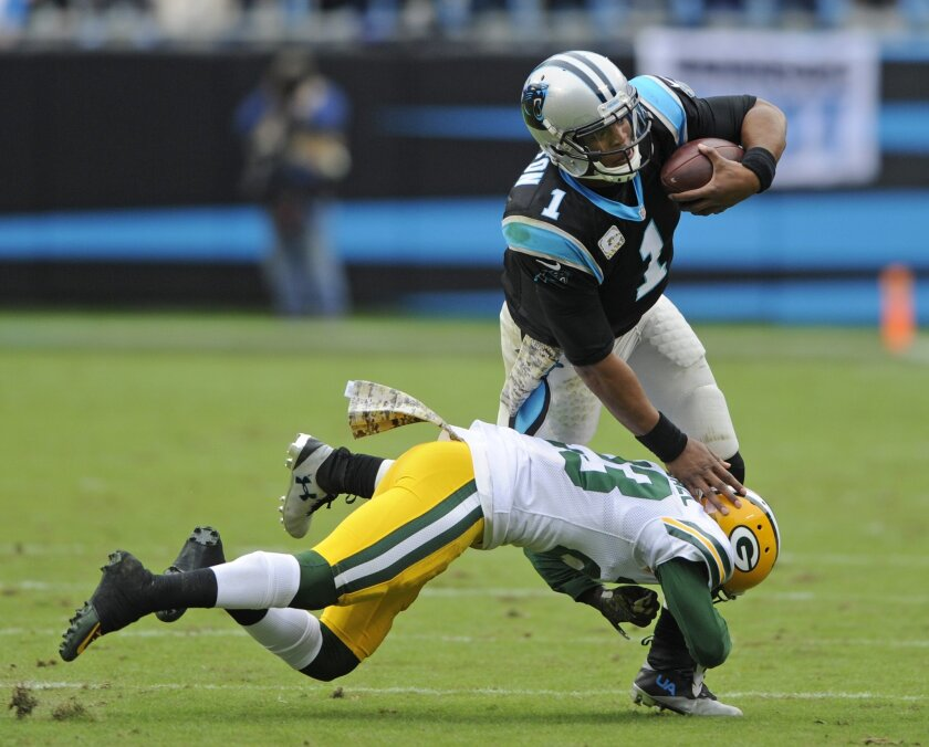 Carolina Panthers' Cam Newton (1) is tackled by Green Bay Packers' Damarious Randall (23) in the first half of an NFL football game in Charlotte, N.C., Sunday, Nov. 8, 2015. (AP Photo/Mike McCarn)