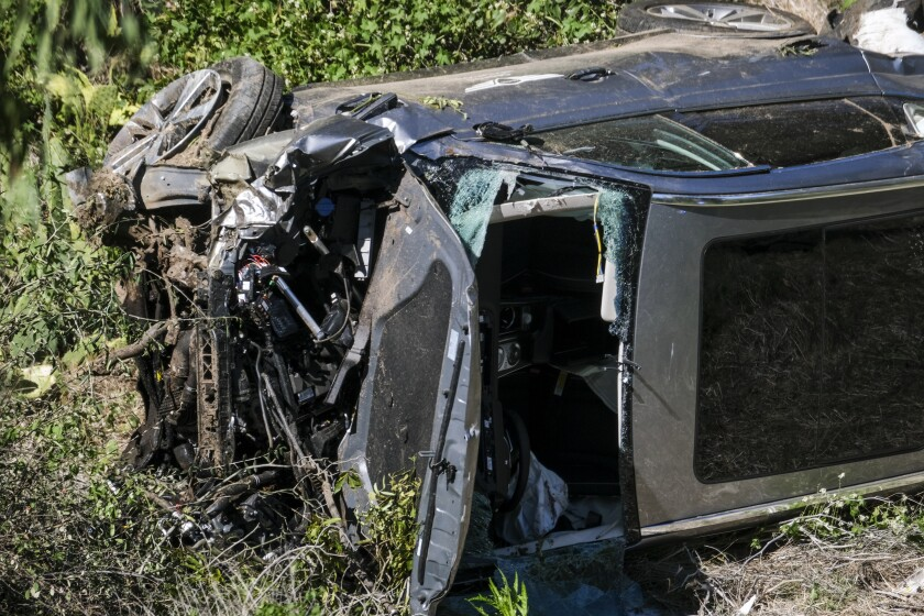 A vehicle with extensive front-end damage and its windshield removed rests on its side after an accident.