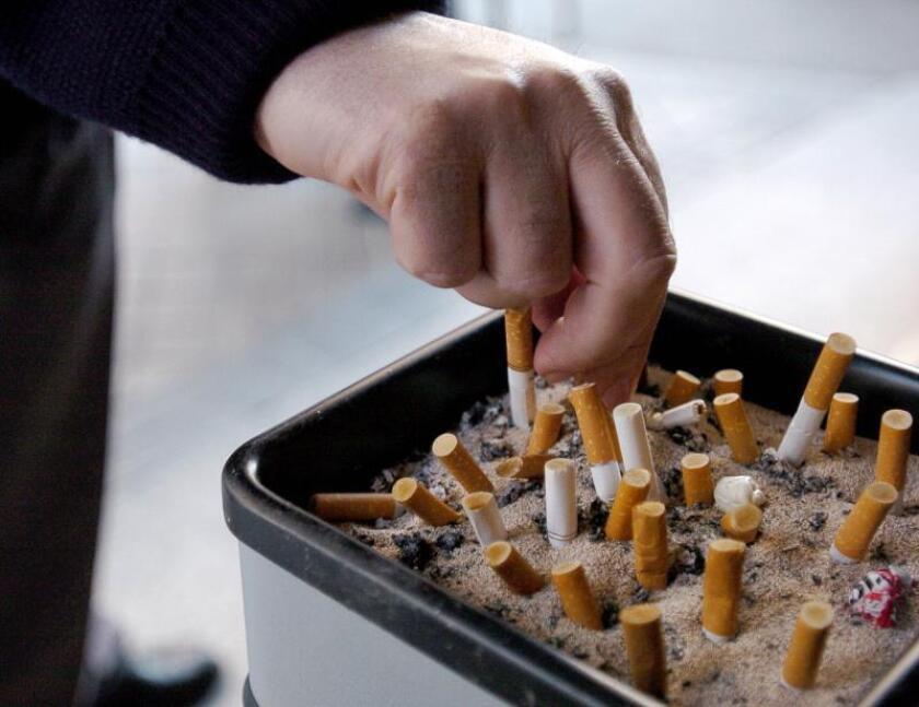MD16 Madrid, 5.01.06.- Un hombre apaga un cigarrillo en un cenicero instalado en la entrada de su centro de trabajo en la primera semana de aplicación de la ley antitabaco que prohibe esta actividad en este tipo de lugares. EFE/Victor Lerena
