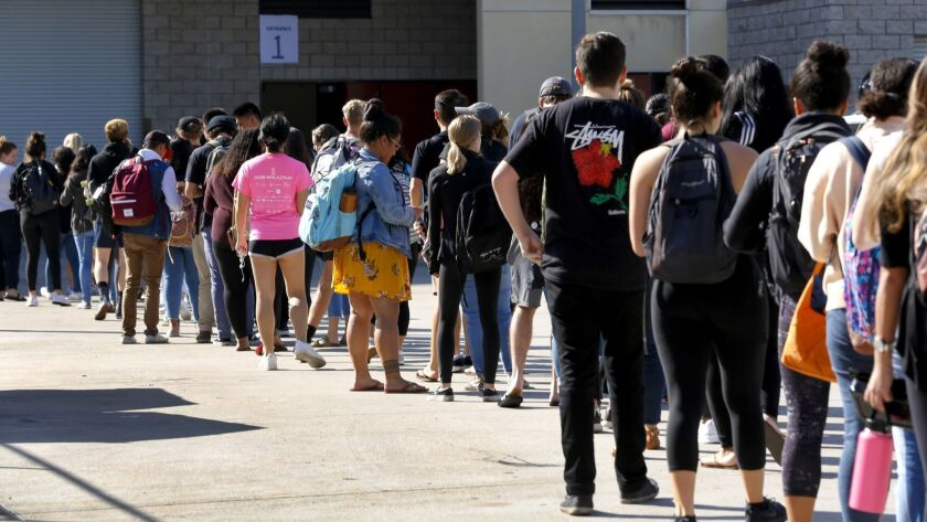 Students stand in line at Viejas Arena on SDSU campus to receive the vaccination on Monday morning a