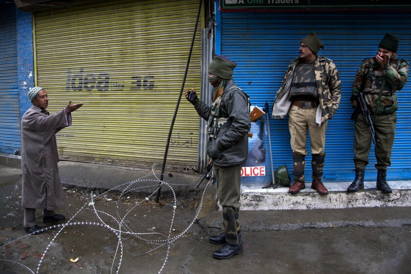 Indian paramilitary soldiers ask a Kashmiri Muslim man to turn back at a temporary check post during a curfew in Srinagar, Indian controlled Kashmir, Thursday, Feb. 11, 2016. Authorities have imposed curfew on movement of people in some parts of Indian-controlled Kashmir after separatist leaders ca