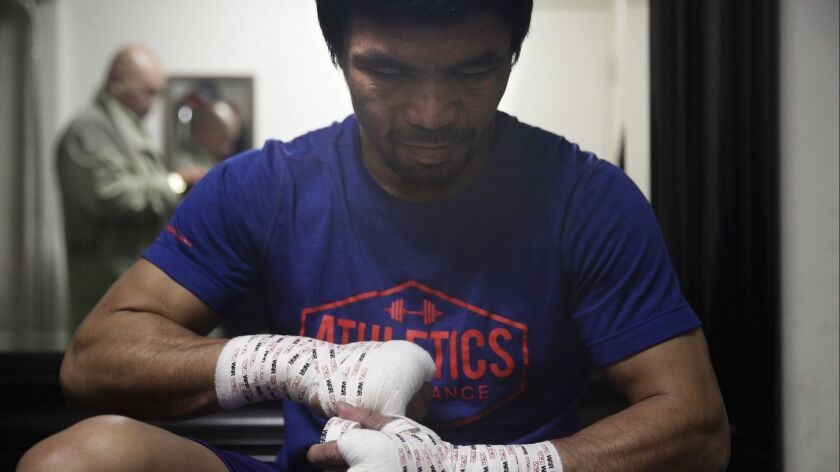 Manny Pacquiao tapes his hands for a workout at the Wild Card boxing club on Jan. 14.