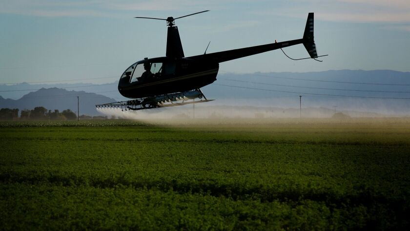 A helicopter sprays insecticide on a field outside El Centro in the Imperial Valley in 2015.
