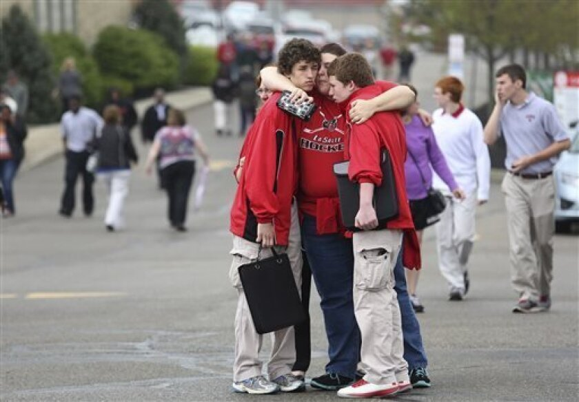 Students and family console each other outside La Salle High School, Monday, April 29, 2013, in Cincinnati, where a student pulled out a gun and shot himself in a classroom. La Salle High School west of Cincinnati was locked down until after police arrived and determined there was no threat to othe