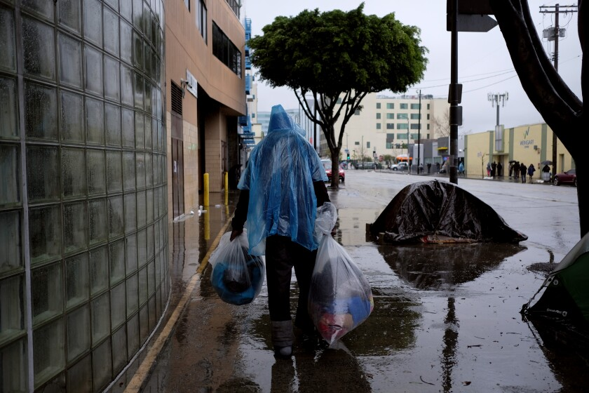L.A. officials are opening winter shelters early as storms hit the region. Above, a homeless man last winter in downtown Los Angeles.